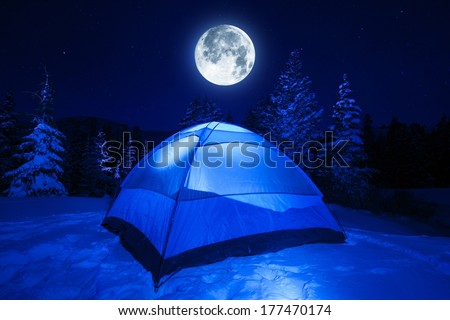 Winter Night Camping in Heavy Mountains Snow. Large Full Moon on the NIght Sky. Outdoor and Recreation Theme.