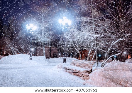 Winter night landscape - bench under winter trees and shining street lights with falling snowflakes #487053961