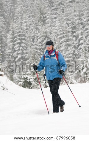 Winter Nordic Walking - female trekking in winter mountains