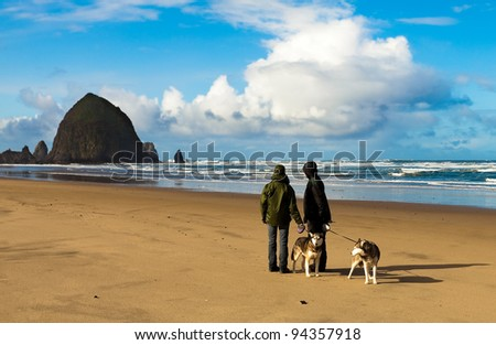 Winter ocean and beach scene. Dog walkers looking at dramatic view of Haystack Rock in Cannon Beach on the Oregon coast.