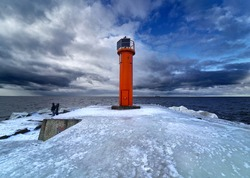 Winter on shore of the Baltic Sea. Lighthouse in ice