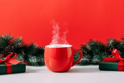 Winter or christmas cozy composition, steaming cup coffee or hot drink, Xmas decoration, branch fir, gift, on red background. Christmas, New Year, winter concept. Front view, copy space