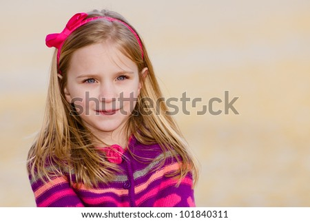 Winter or early spring portrait of pretty young girl child wearing knit poncho at park