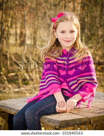 Winter or early spring portrait of pretty young girl child wearing knit poncho at park while showing off temporary peace tattoo