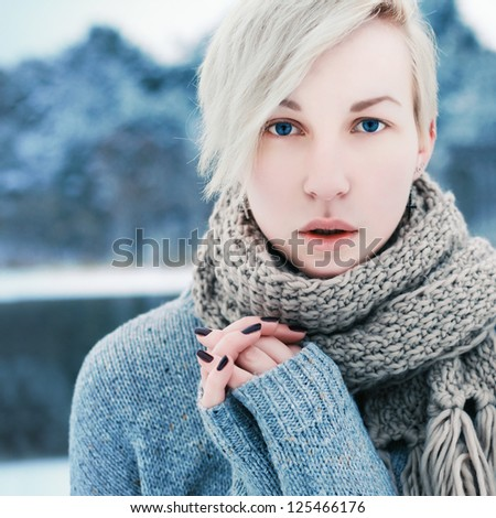 Winter outdoor closeup portrait of young sensual blonde woman. Girl poring in winter park, blue cold colors.