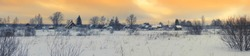 Winter panorama with beautiful sunset over the russian village and the snow-covered field under an orange sky