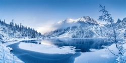 Winter panoramic landscape with scenic frozen mountain lake and clear blue sky. Alps, Switzerland.