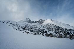 Winter panoramic view of Lomnicky Peak. Ski resort Tatranska Lomnica. Hight Tatras, Slovakia. Slope on a ski tour in winter. skiing and trekking concept.