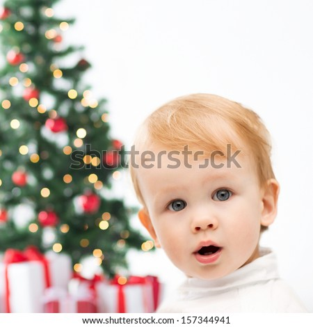 winter, people, x-mas, happiness concept - happy little boy with christmas tree and gifts
