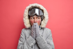 Winter photo of frozen ethnic woman warms up freezing hands by blowing hot air feels cold during frosty day dressed in warm coat has active rest wears ski goggles isolated on pink background