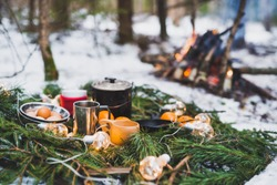 Winter picnic in the snow near by campfire with oranges and tea. Christmas garlands on fir branches
