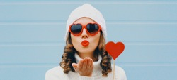 Winter portrait close up of woman with red heart shaped lollipop blowing red lips sending sweet air kiss wearing a white hat, sweater over blue background