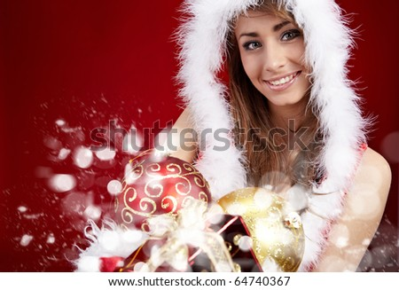 winter portrait of a beautiful young smiling woman with a gift in her hands