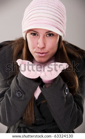 winter portrait of a beautiful young woman with a cap and a scarf