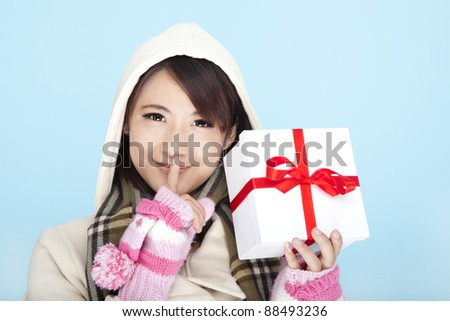 winter portrait of a smiling woman with a gift box - stock photo