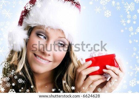 winter portrait of a smiling woman with a gift in her hands and snowflakes