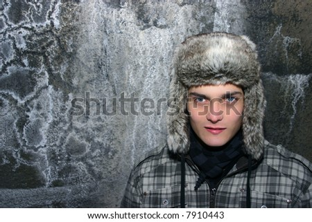 winter portrait of a young man with fur cap
