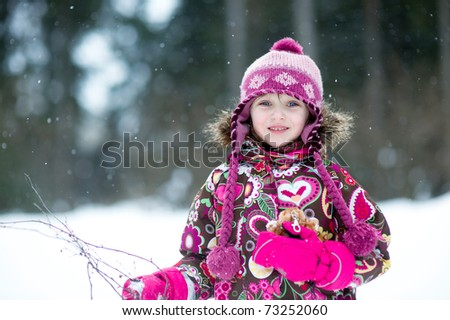 Winter portrait of adorable little girl in colorful pink and brown jacket in the country