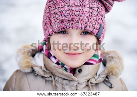 Winter portrait of adorable small girl with blue eyes in pink hat looks into the camera