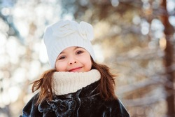 winter portrait of adorable smiling child girl in white hat on the walk in snowy forest. Outdoor activity on holidays.