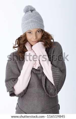 Winter portrait of attractive girl in hat and warm clothes, over white background.