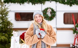 Winter Portrait Of Beautiful Blonde With Red Coffee Mug In Hands Standing Outdoors At Campside Over Modern RV Trailer Background, Enjoying Camping During Cold Weather And Christmas Holidays