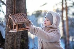Winter portrait of cute child in snow Garden. А  child feeds birds in the winter forest