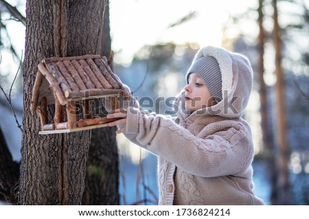 Winter portrait of cute child in snow Garden. А  child feeds birds in the winter forest Сток-фото ©