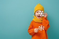 Winter portrait of happy child wearing knitted hat, snood and sweater. Girl having fun, playing and laughing on teal background. Fashion concept.