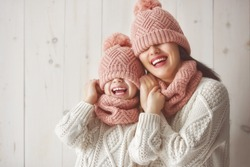 Winter portrait of happy loving family wearing knitted hats, snoods and sweaters. Mother and child girl having fun, playing and laughing on white wooden background. Fashion concept.