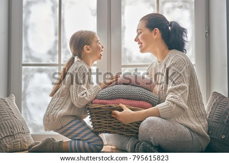 Winter portrait of happy loving family wearing knitted sweaters. Mother and child girl having fun, playing and laughing at home. Fashion concept.