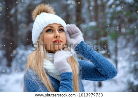 Stock Photo Winter portrait of smiling beautiful blonde girl in white hat and gloves under the snow - closeup beauty photo.