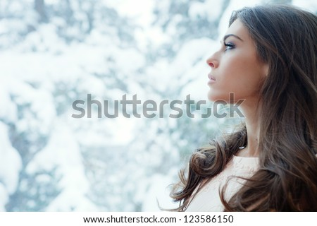 winter portrait of young woman by window