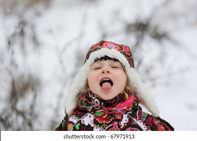 Stock Photo: Winter portrait of small girl in colorful snowsiut and warm hat
