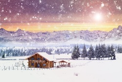 Winter postcard of cottage in the mountains at sunrise. Christmas concept.