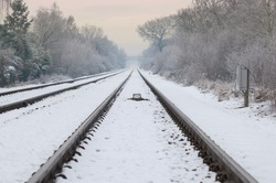 winter railroad track diminishing into a distant hazy sunset (portrait crop also available)