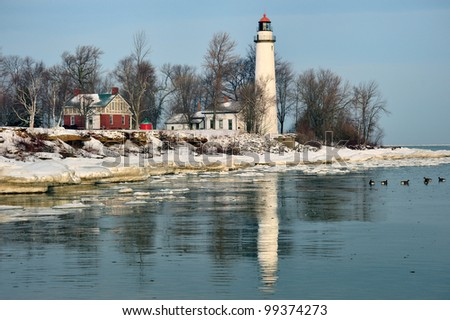 Winter reflections at Point Aux Barques Lighthouse. Geese in the cold water of Lake Huron, Port Hope, Michigan USA