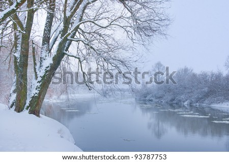 winter river when it is snowing - stock photo