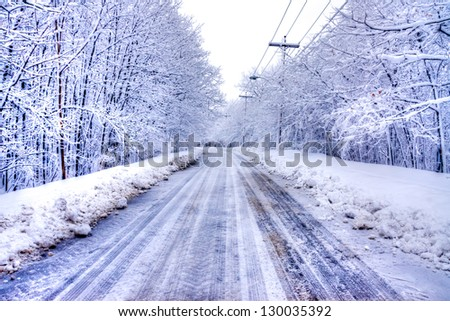 Winter Road in Snowy forest in blue tone with electric post.