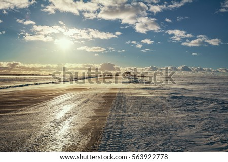 Stock Photo Winter road, the bright sun, snow drifts and blowing snow, white clouds in the distance, the beautiful landscape, frost and cold