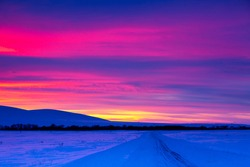 Winter road with mountain during amazing vivid saturated beautiful sunset sky in pink, purple and blue colors. Sunset background