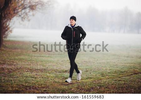 Winter runner. Man running in the park at cold morning.