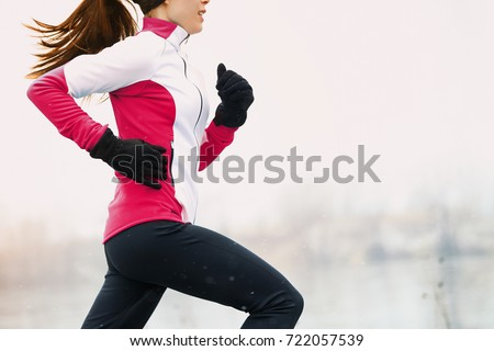Winter running athlete woman on cold run jogging fast with speed and sprint on outside workout wearing warm clothing gloves, winter tights and wind jacket in snow weather. #722057539