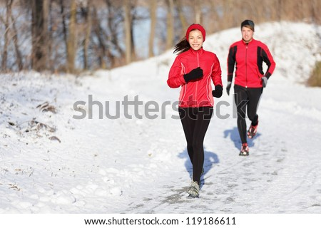 Winter running exercise couple. Runners jogging in snow. Young asian woman fitness model and caucasian man. - stock photo