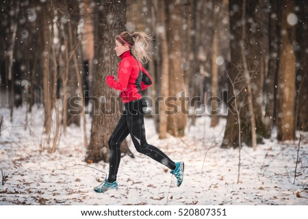 Winter running exercise. Runner jogging in snow. Young woman fitness model running in a city park