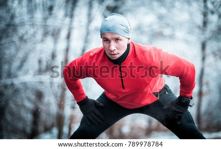 Winter running exercise, runner stretching on road in the snowy forest