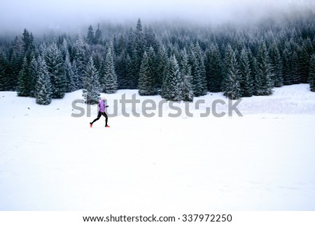 Winter running woman. Sport, fitness, jogging inspiration and motivation. Young happy woman cross country running in mountains on snow, winter day. Female trail runner working out, jogging exercising.