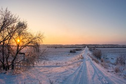 Winter rural, country road on hill in field covered by snow at sunset with the sun shining through the trees with sky gradient