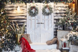 Winter rustic interior decorated for New year with artificial snow and Christmas tree. Winter exterior of a country house with Christmas decorations in rustic style. Christmas eve
