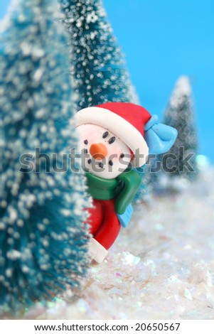 winter scene in glitter, a snowman  is playing hide and go seek, peeking or hiding  behind miniature pine trees